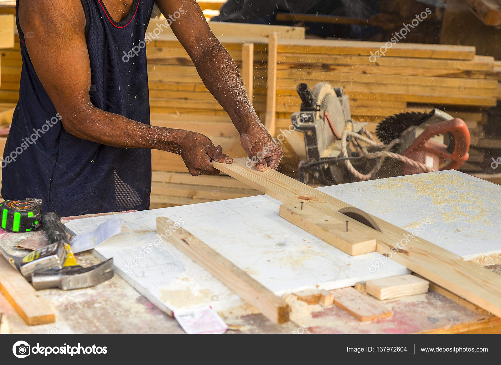 Senior male carpenter using table saw for cutting wood at worksh ...
