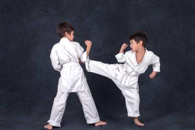two boys of the karate in a white kimono battle or train