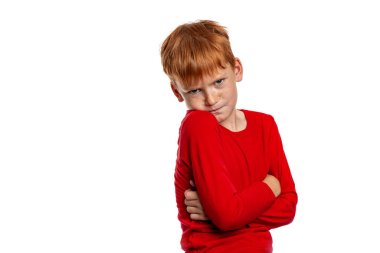 Waist up portrait of young red-haired hurting boy wearing  red shirt, isolated on white
