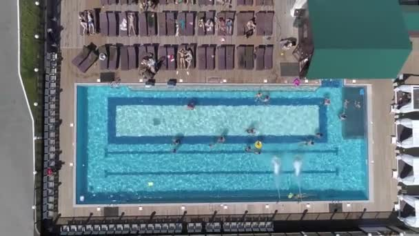 Top down aerial view of modern recreation center with a pool. People relax, swim and lie on sun loungers.