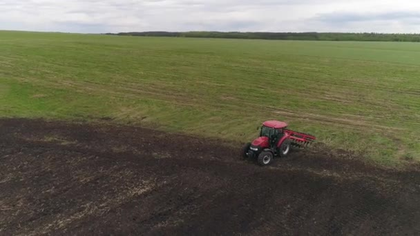 Aerial view of tractor cultivates farm field for sowing. Farm tractor with rotary harrow plow preparing land for sowing. Cultivation of farmland by disc harrows.