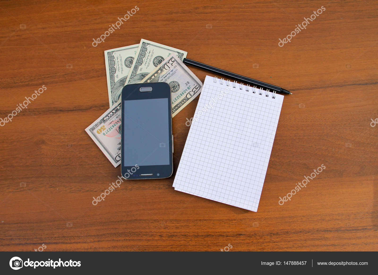 Bloc notes avec stylo smartphone et dollar cash sur le bureau en
