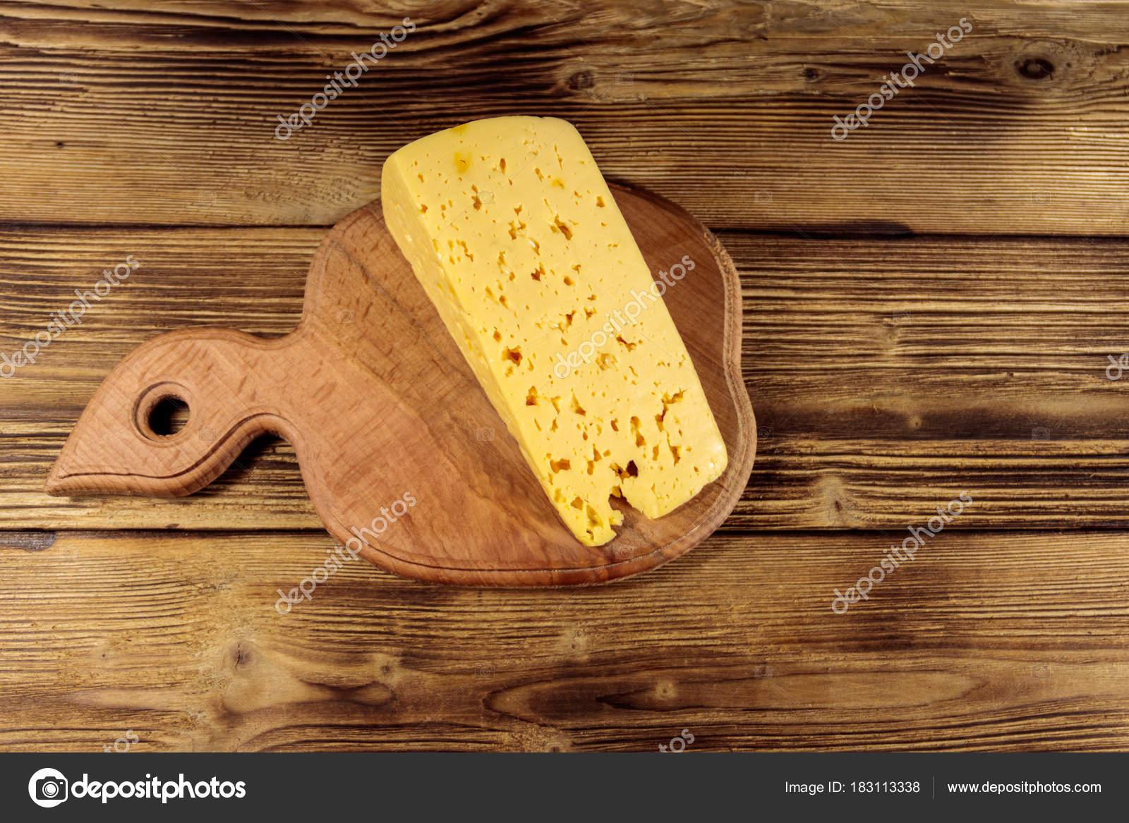Stück Käse auf Schneidebrett auf Holztisch — Stockfoto ...