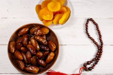 Dried apricots and dates fruit with wooden rosary on white wooden table