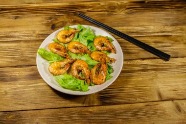 Tasty baked shrimps on a wooden table