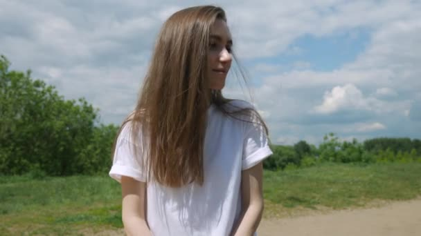 Close up portrait of young girl with long hair in white t-shirt, turning head and looking in camera, smiling. Summer sunny day 4K video.