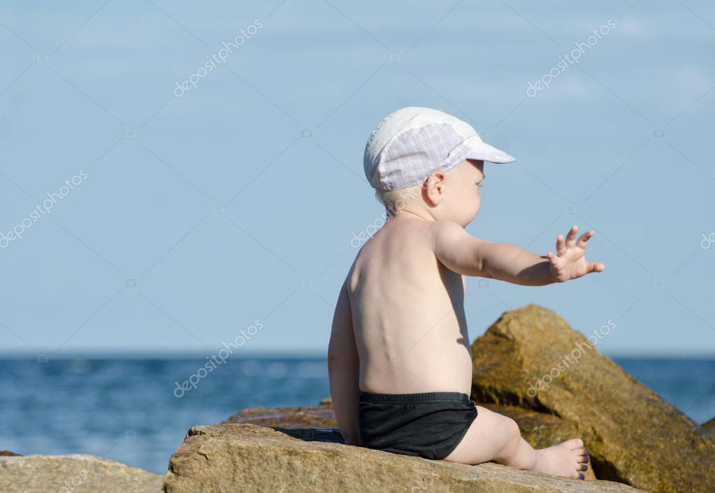 Gesture not to bother. Little boy in swimming trunks sits on the seashore, place for text