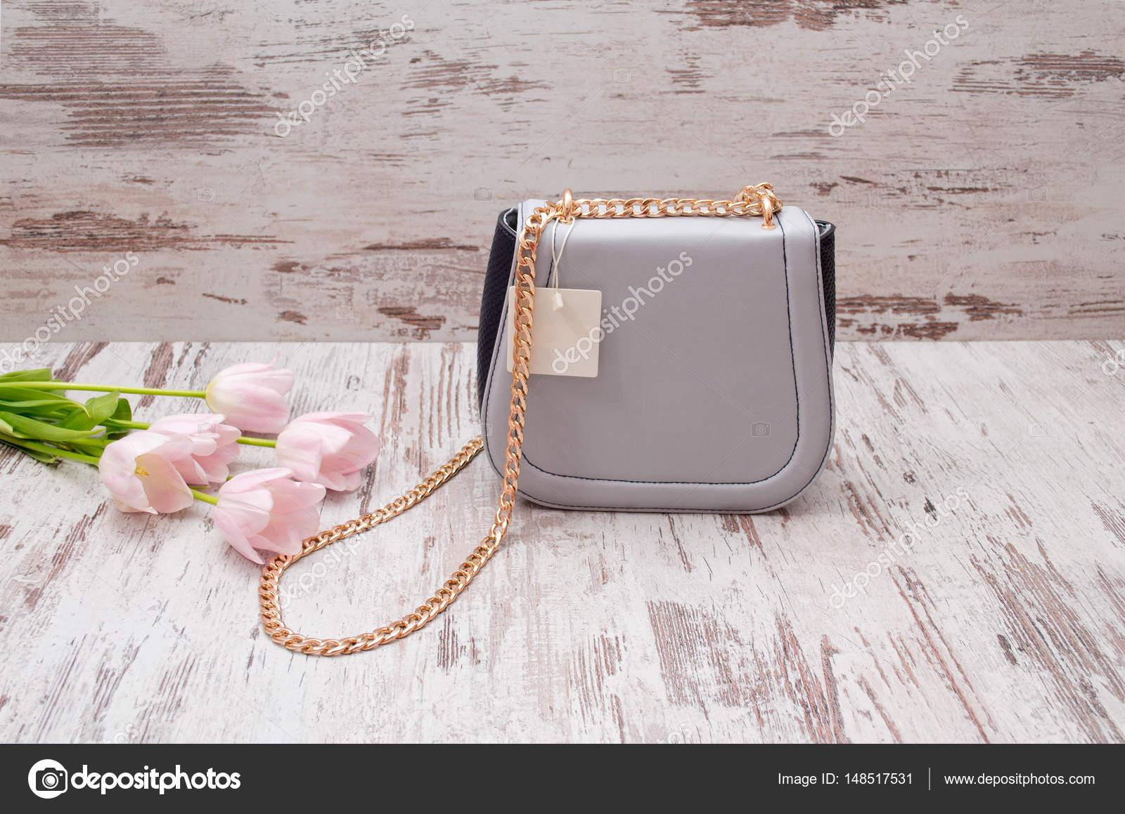fdb725e3cb Μικρό γκρι τσάντα με έναs τιμή tag σε ένα ξύλινο πλαίσιο
