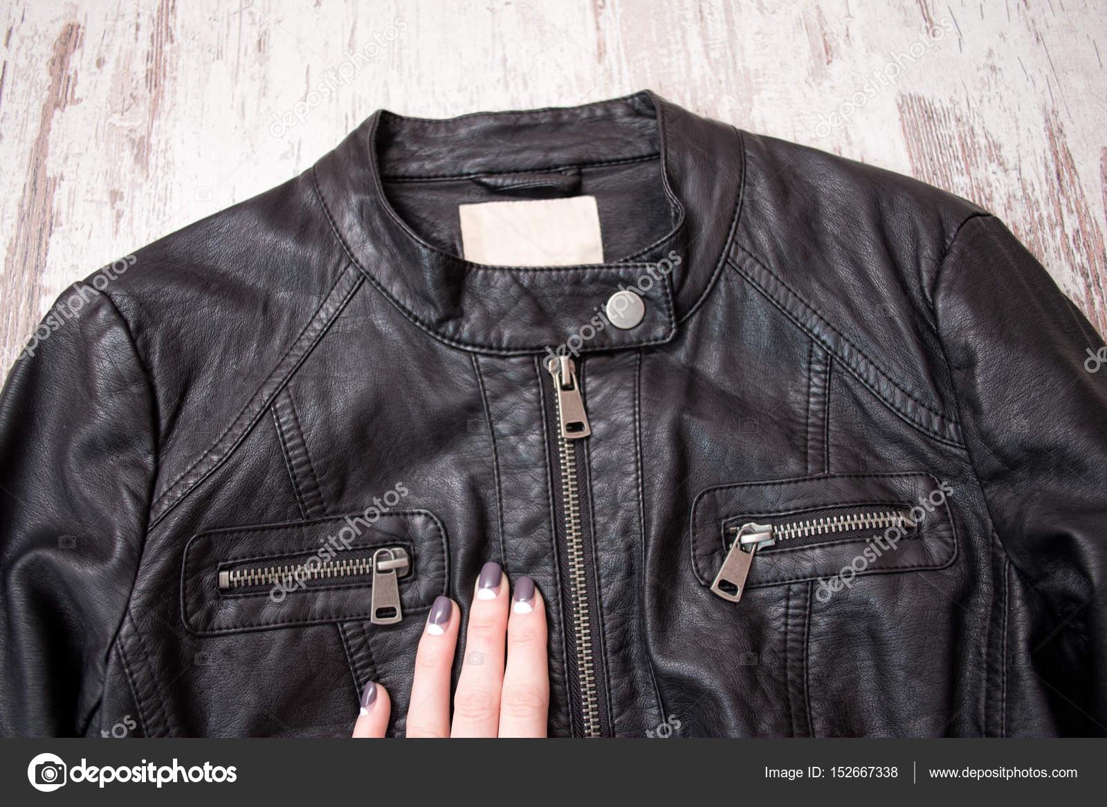 Μαύρο δερμάτινο μπουφάν με φερμουάρ και ένα γυναικείο χέρι. Έννοια της  μόδας 04249a817f9