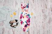 Bílé šaty v květiny, černé boty a půlky pomeranče. Dřevěné pozadí, módní pojem