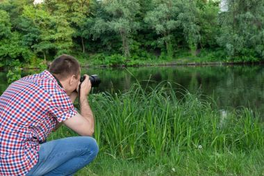 Photographer is shooting on the background of the river
