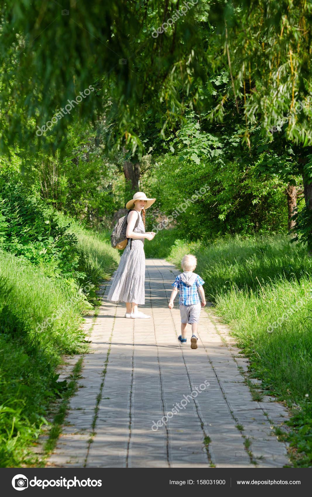 Mutter und Sohn zu Fuß entlang der Straße in den Park. Hinten Sie ...