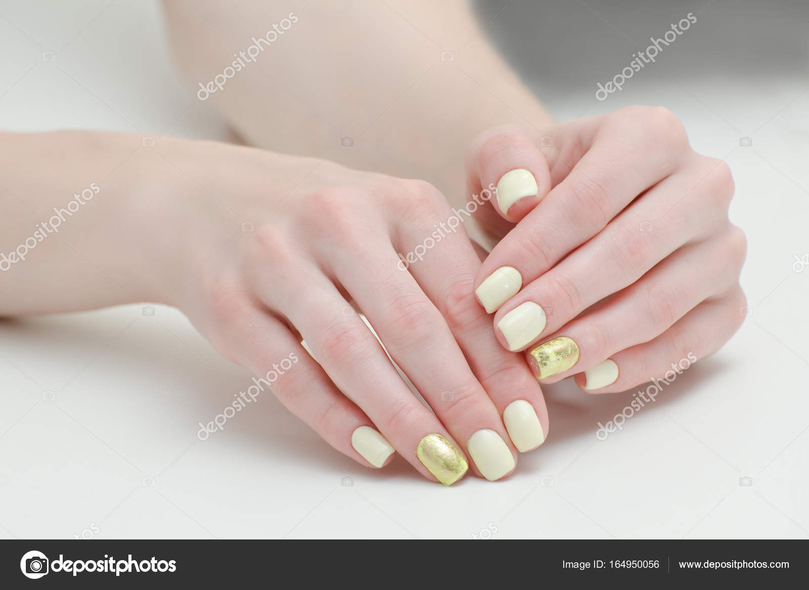 Beautiful Female Hands With A Manicure On Light Background Yellow Gold Nails Photo By SomeMeans
