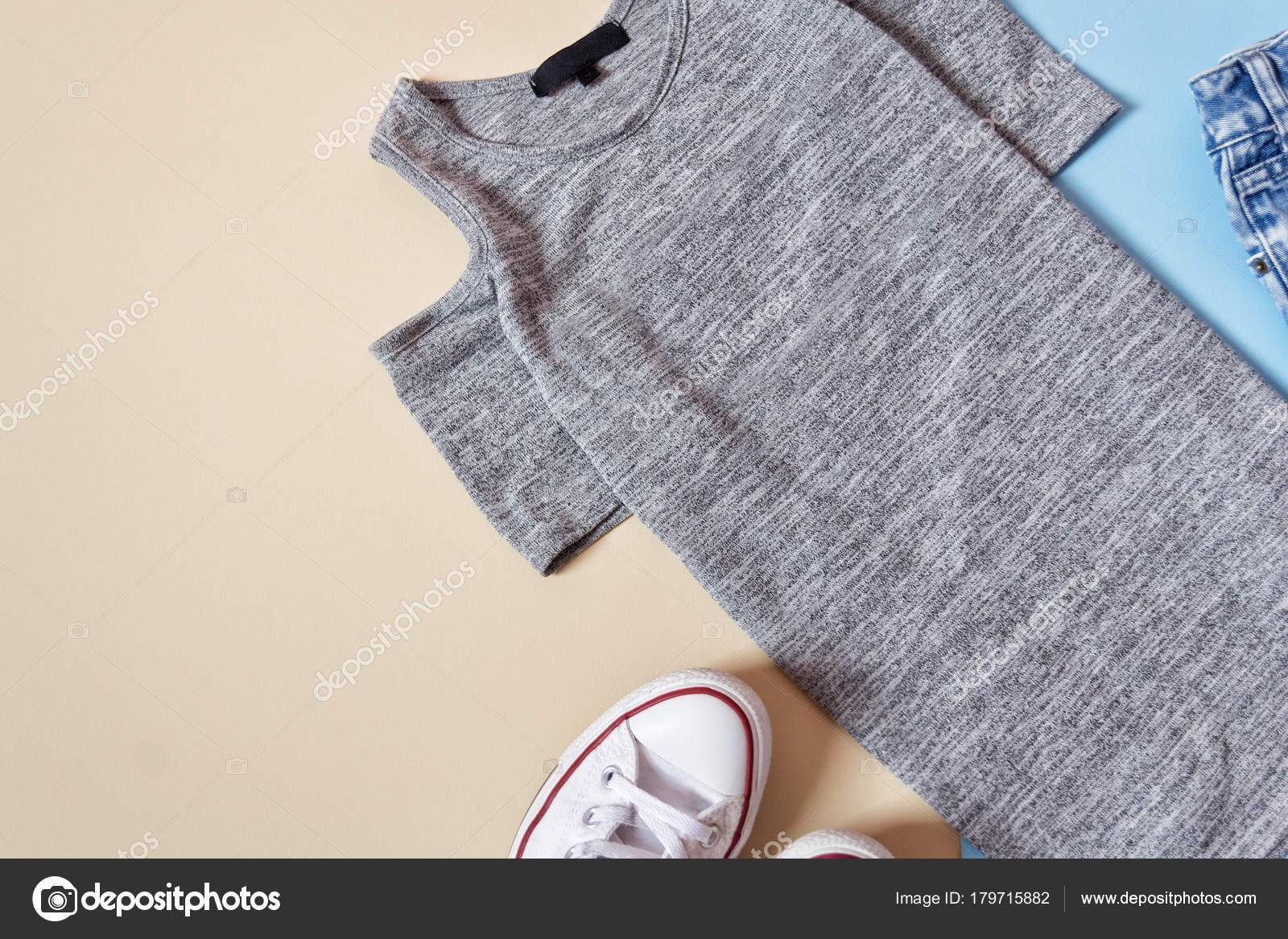 7dd826d8a3 Conceito de moda. Estilo urbano feminino. Vestido cinza e tênis branco  sobre um fundo