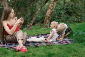 Young mother taking pictures of their children on phone. Picnic with the whole family