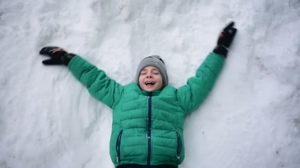 Child boy lies on snow and makes snow angels. Child enjoys the snow. Slow motion