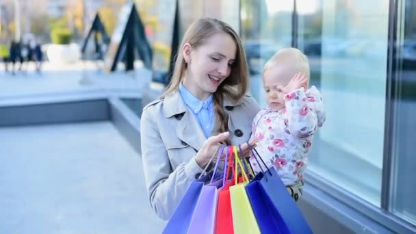 Matka a dítě po nakupování. Dítě si hraje s matčinými nákupy. Máma drží dítě a mluví s ním.