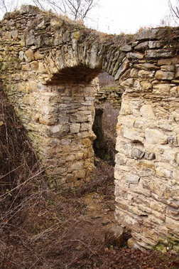 Old ruined wall with door passage