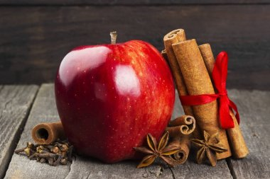 Apple, cinnamon, anisetree on a dark wooden background