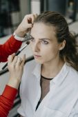 Photo Portrait of a young girl doing make-up in a beauty salon. Series makeup before and after