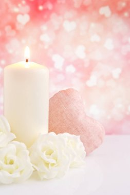 Valentine's hearts and candle with a bright glittering background