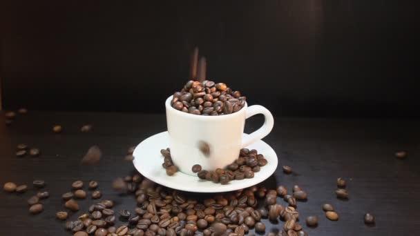 Kávová zrna na tmavém pozadí. Zpomalený pohyb