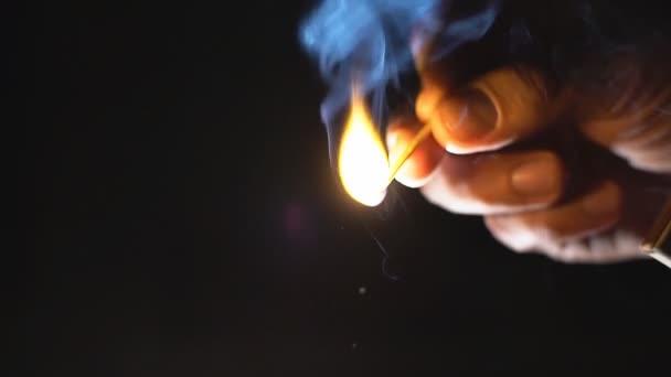 Primo piano della mano maschio luci una corrispondenza. Slow motion