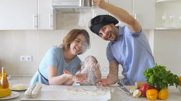 Šťastná rodina je vaření v kuchyni. Táta Sifts mouky pomalý pohyb
