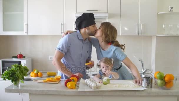 Mladá rodina tráví čas v kuchyni.