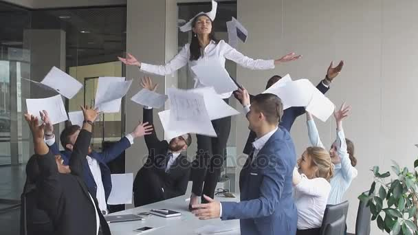 Happy successful business people in office having fun throwing documents, slow motion.