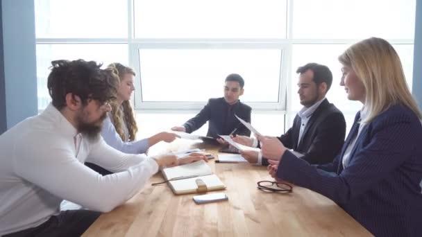 Skupina mladých podnikatel k jednacímu stolu v kanceláři. Kolegové se podívat přes dokumenty. obchodní jednání