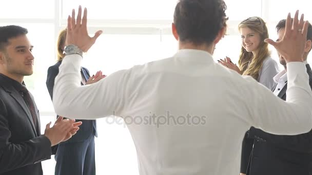 group of businessmans celebrating a success. the man give a high five to a colleague. slow motion