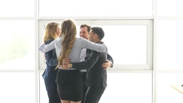 group of young business people celebrating success. colleagues hugging and joyfully celebrate the victory. slow motion