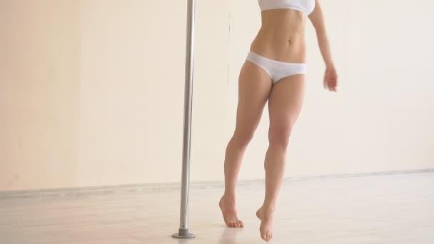 Dívka, tanec na tyči. krásná mladá dívka dělá cvičení na pólu. Zpomalený pohyb