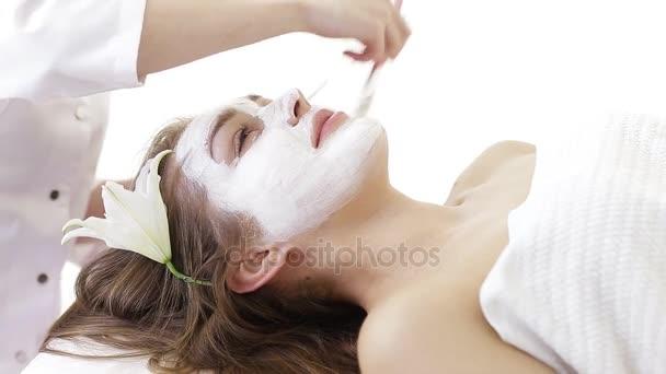 junge Frau bekommt Gesichtsmassage im Wellness-Salon