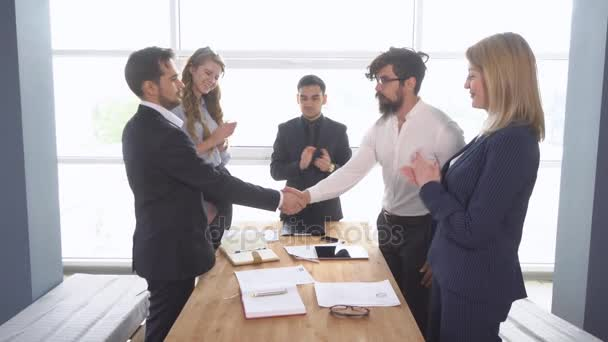 Handshake of businessman at the conclusion of the transaction. business meeting. Successful negotiations of a group of young businessman in the office of the company