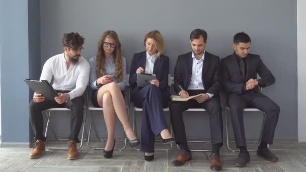 nezaměstnaní, že rozhovory sedí na židlích v chodbě budovy úřadu.