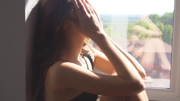 Krásná brunetka v prádle sedí na podlaze a pláč
