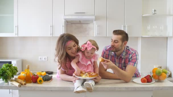 Boldog család eszik süteményt, a konyhában.