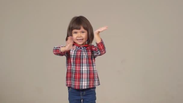 legrační malá dívka pózuje na kameru. portrét šťastné, bezstarostné dítě. dívka v košili a džínách