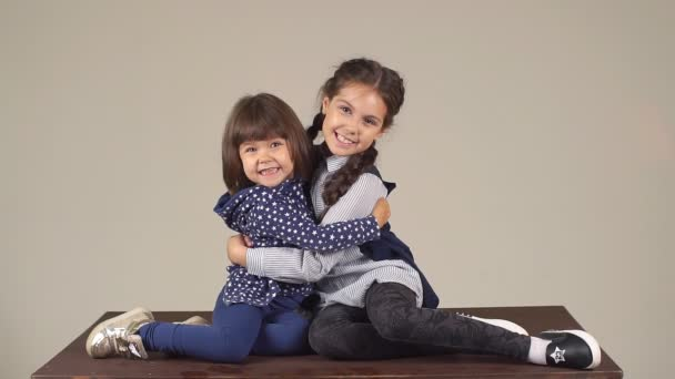 two little girlfriends are embracing and smiling. friendship and love little sisters. slow motion
