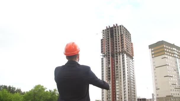 Portrét šťastný a sebevědomý architekt s ochrannou přilbu ve staveniště. Zpomalený pohyb