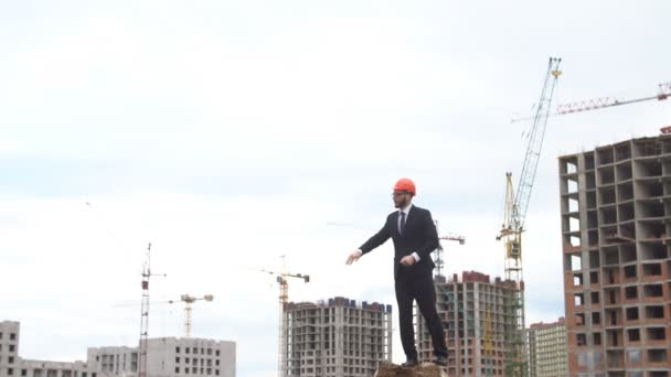 Engineer using gestures gives instructions at the construction site.