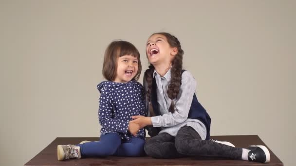 Two little sisters embracing and smiling. Slow motion