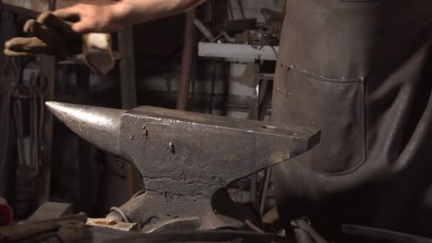 Smith cleans the anvil