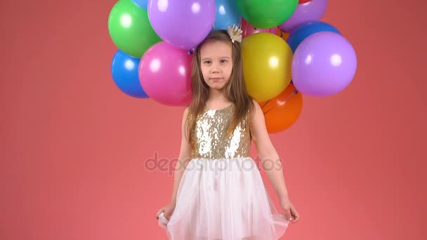 Child with colorful balloons. Little girl winks and smiles. slow motion