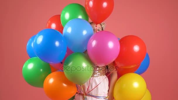 Dítě s barevnými balónky. Malá dívka mrknutí a úsměvy. Zpomalený pohyb