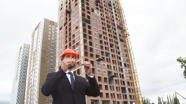 Portrét muže architekta. Mladí lidé na staveništi.