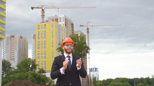 Mladý inženýr vítá a ukazuje palec