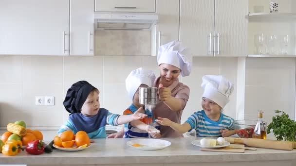 children cook in the kitchen with mom. three small children made a mess on the kitchen table